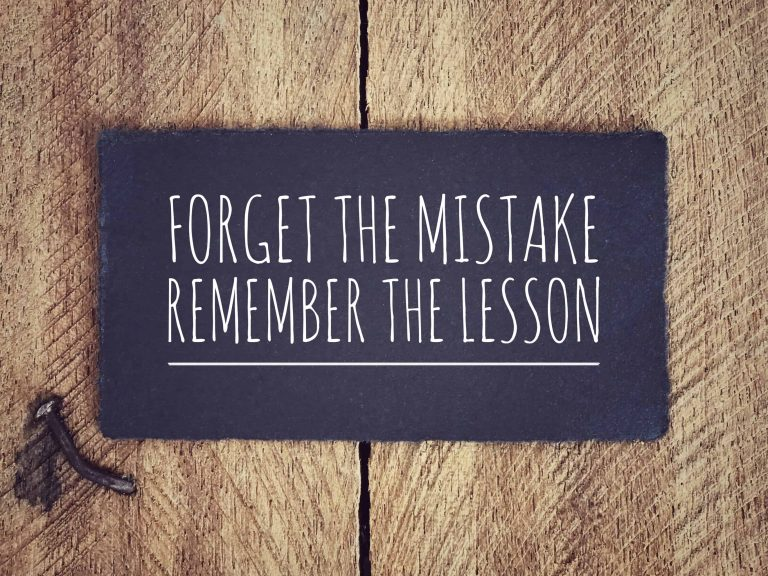 "startup coach advice on a board that reads ""forget the mistake, remember the lesson"""